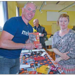 John McKenzie of 'Just Books' Lakes Entrance selling Jill Herman a copy of 'Dark Emu'.